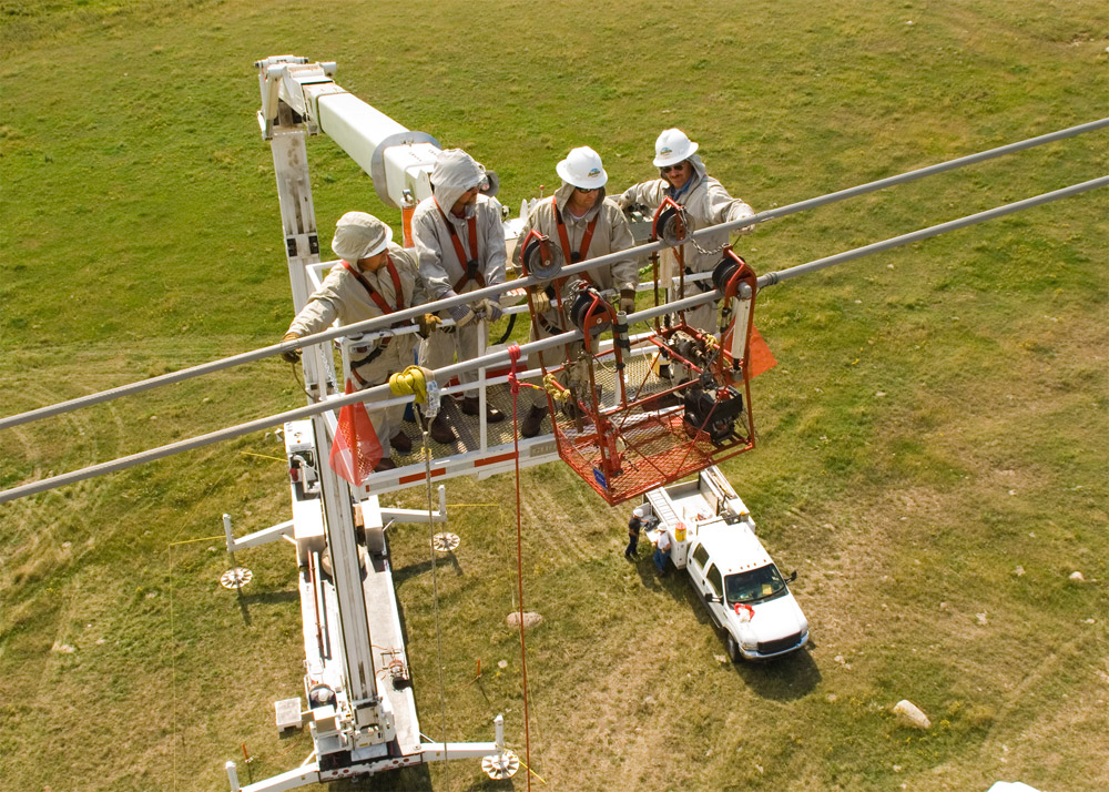 Basin Electric Power Cooperative Linemen work on a high-voltage transmission line from a bucket truck.