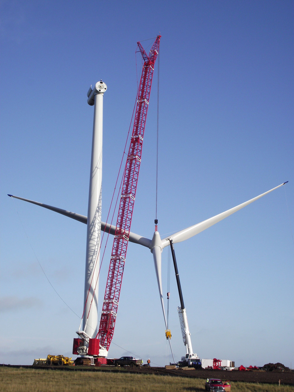 The blades are raised by crane to be attached to the nacelle.