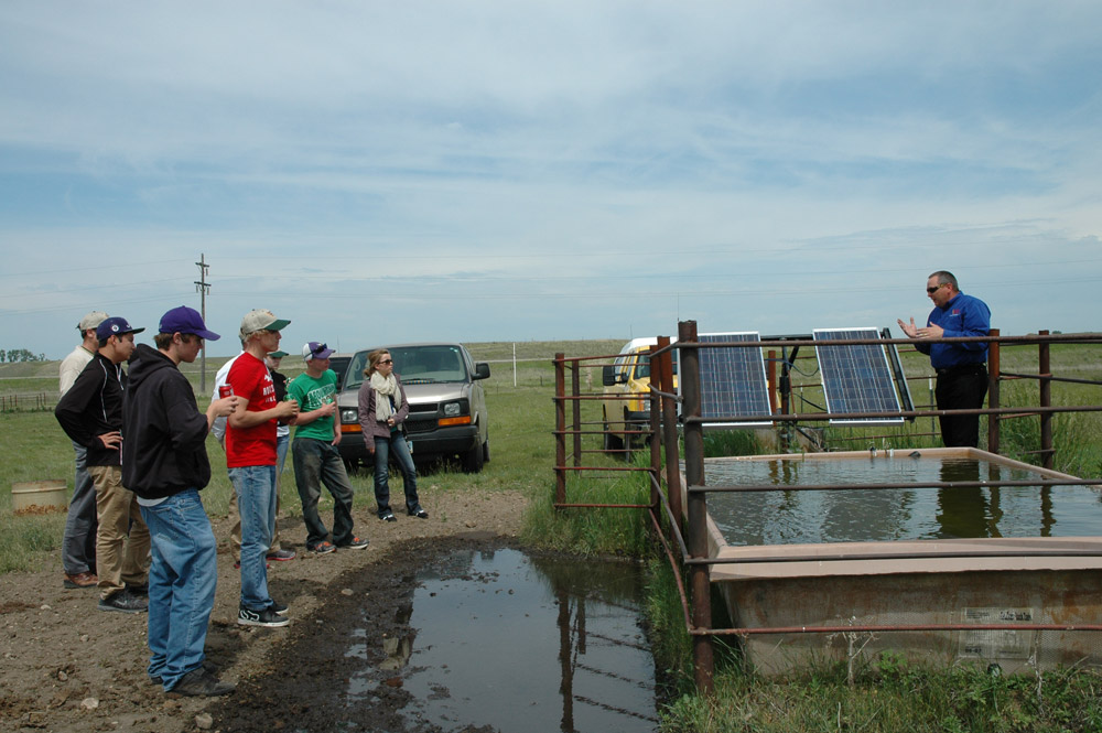 Tom Jesperson of Verendrye Electric explains to students that solar energy is used to pump water for cattle to drink