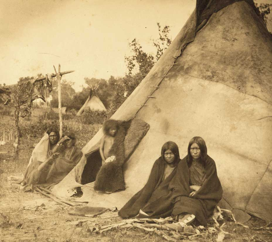 This family poses for a photo next to their tipi home