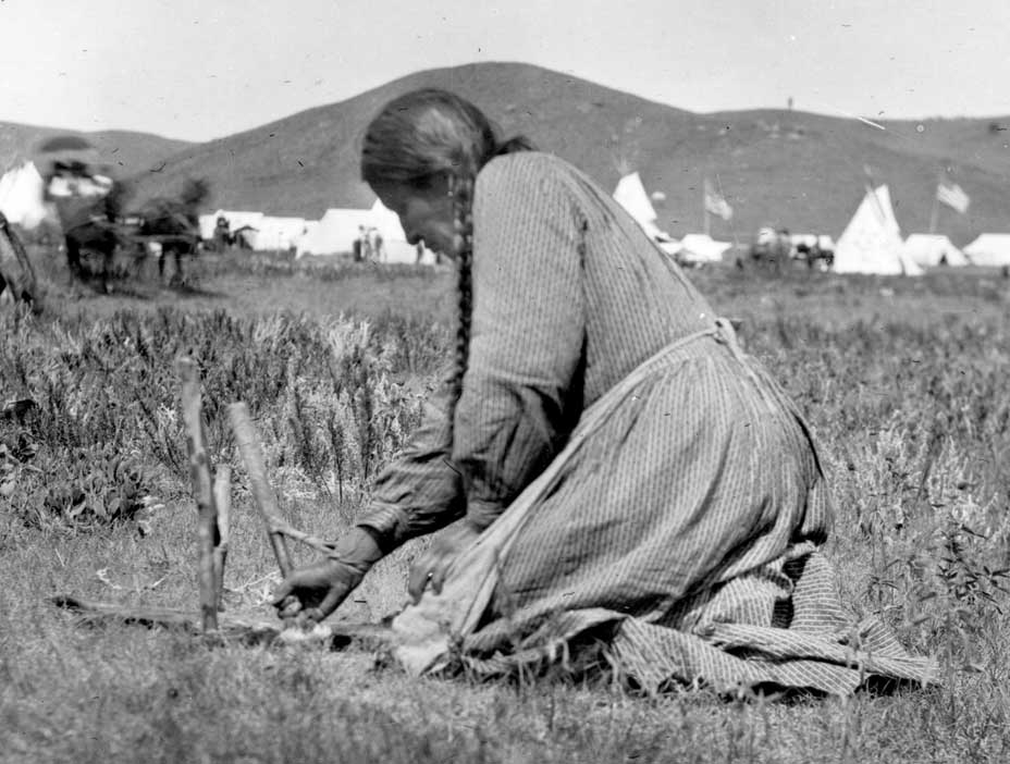 Sioux woman fleshing out a bison hide