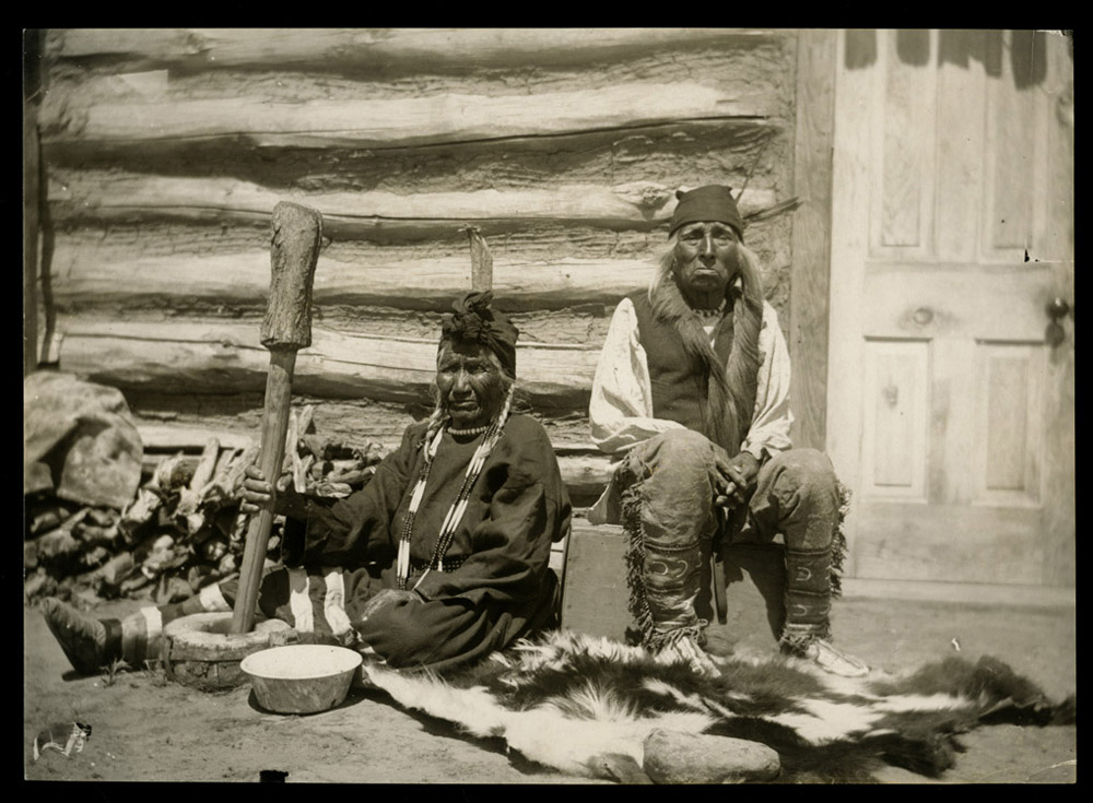 Yellow Nose sits with her husband Bear on the Water in front of their home while she uses a mortar to pound dried corn into flour.