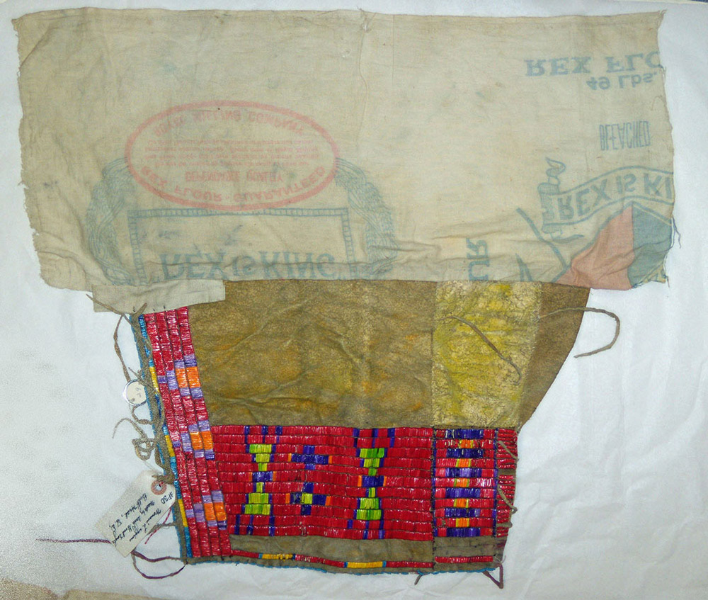 Indians who traded with European Americans received all kinds of manufactured goods in exchange for furs.  Indians sometimes re-used the goods in ways that better suited them.  These leggings were made by a Lakota woman, Anne Good Eagle.  She constructed the leggings with a cotton cloth flour sack from the Royal Milling Company and leather. She then decorated them with dyed porcupine quills. The leggings would have been tied around a woman's legs.  Only the decorated leather would show below her skirt.  These leggings are in the collections of the SHSND Museum.