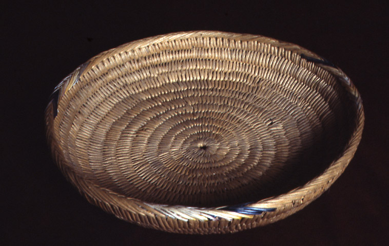 "Baptismal Basket.""  This basket is called pax ruške, or woven platter, in Mandan language.  The basket is about 12 inches in diameter.  It is made of natural plant fibers, such as rushes, and decorated with dyed gull wing feather quills.  Hidatsas picked up feathers shed from Franklin or California gulls to use when decorating baskets or other objects.  The Hidatsa word for gull feather is gawíhgašu.  The Mandan word for gull feathers is ąxká sí.  This basket is like those used in the Mandan adoption ceremony.  The Hoffmans stated that the basket was owned by Mrs. White Face who said it was 60 years old.  The basket was valued at $20 in 1907. SHSND Museum 00560"