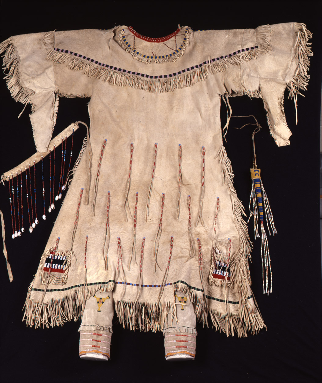"""Young woman's buckskin dress, owned by Spotted Crow Woman.""   This dress was made by Spotted Crow Woman.  A few years later, Mink (Hannah Leavings Grant) wore this dress when she posed for the statue of Sakakawea that now stands in front of the State Historical Society of North Dakota Heritage Center.  The dress was the most highly valued item in the collection at $85. SHSND Museum 01442"