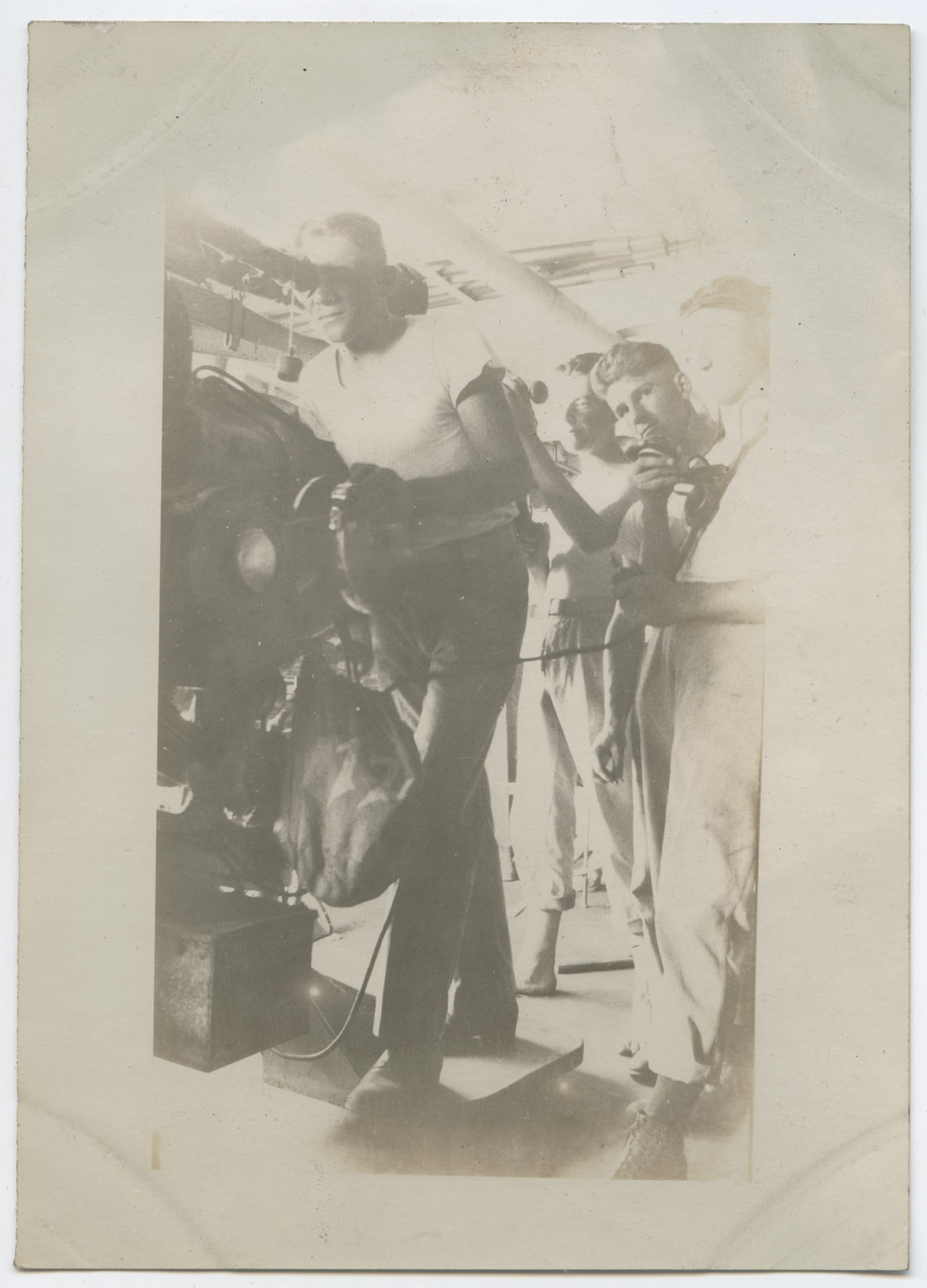 One man checks the sights on the guns while the man behind him reports to other members of the gunnery crew through a communications tube.
