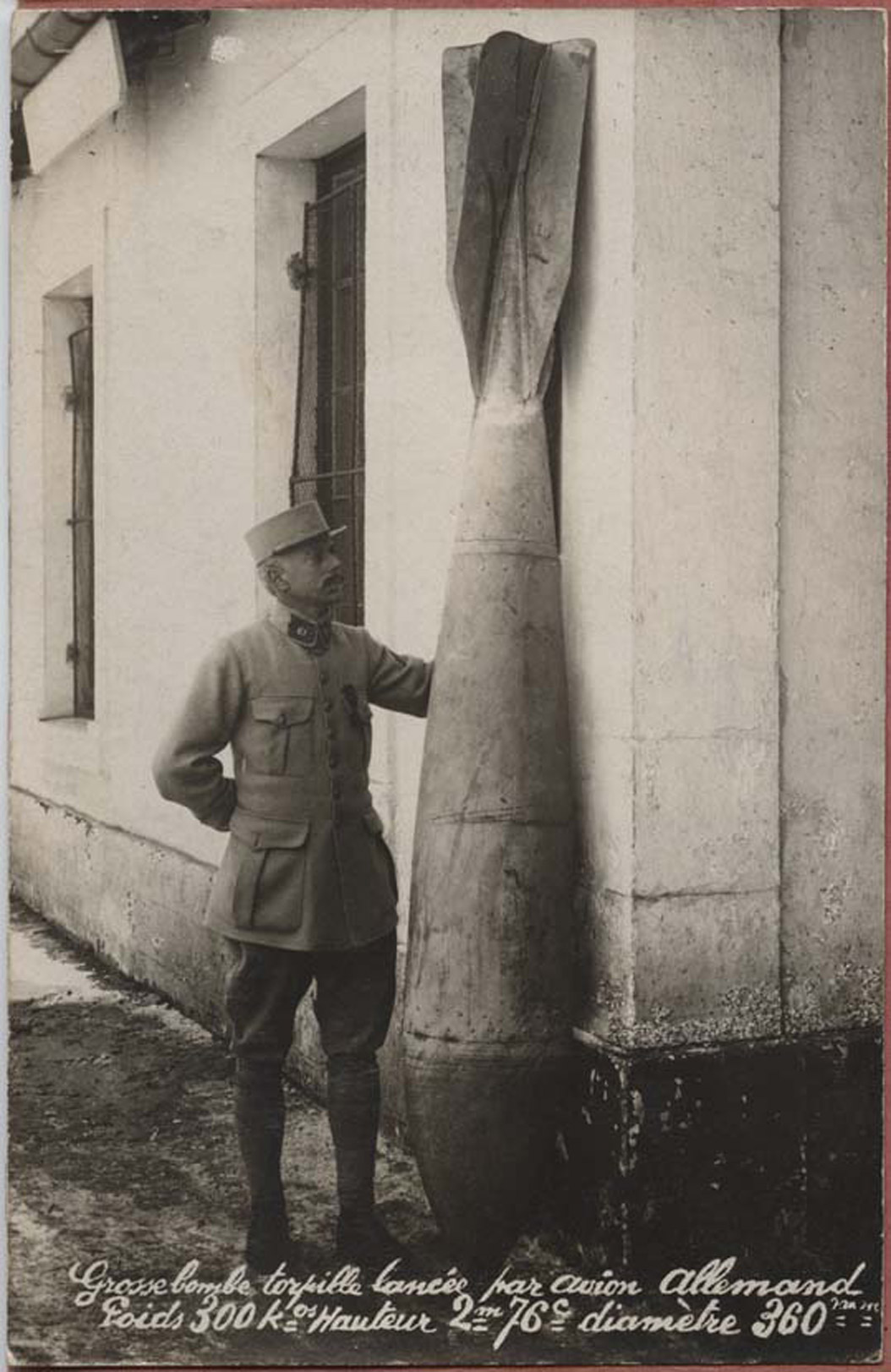 <span class='figure-reader-id'>Image 11:</span> 11086-27-03.  The bombs that fell on Nancy came in all kinds of shapes. In this photo, a soldier stands with this very large bomb. The fact that so many bombs did not explode helped to prevent much damage to the town. <span class='figure-archive-id'>SHSND 11086-27-03.</span>