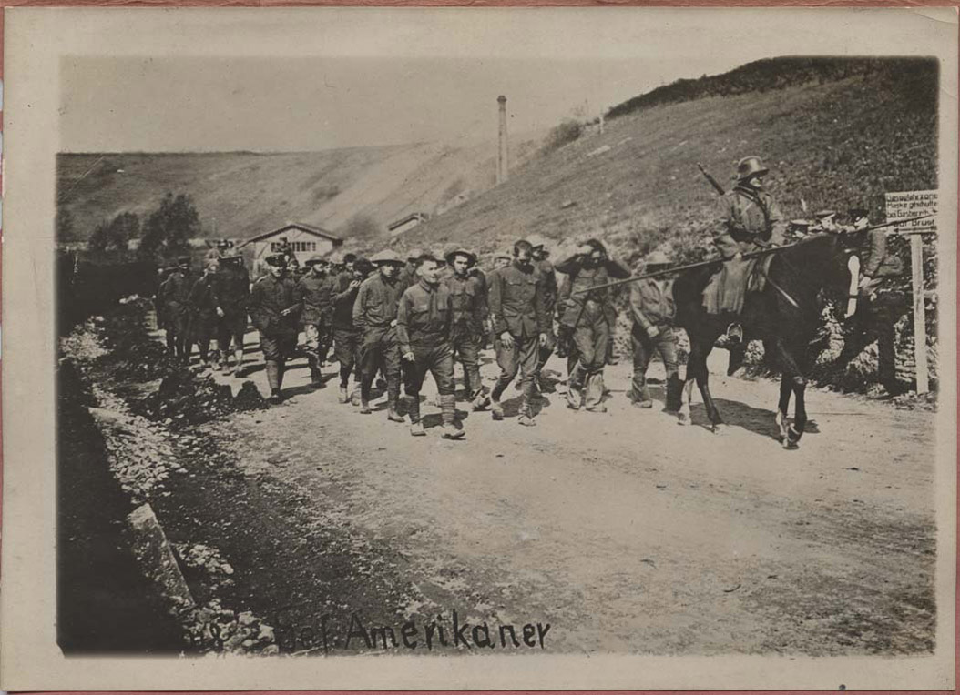 <span class='figure-reader-id'>Image 18:</span> 11086-85-01. When American soldiers were captured they were placed in German prisoner of war (POW) camps. These American soldiers were being marched to prison. The conditions of POW camps and the care of soldiers was governed by international law. <span class='figure-archive-id'>SHSND 11086-85-01.</span>