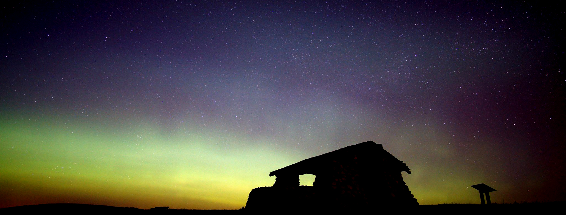The Northern Lights over the silhouette of a building