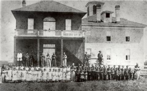 Gray nuns mission school students and nuns standing in front of the school building