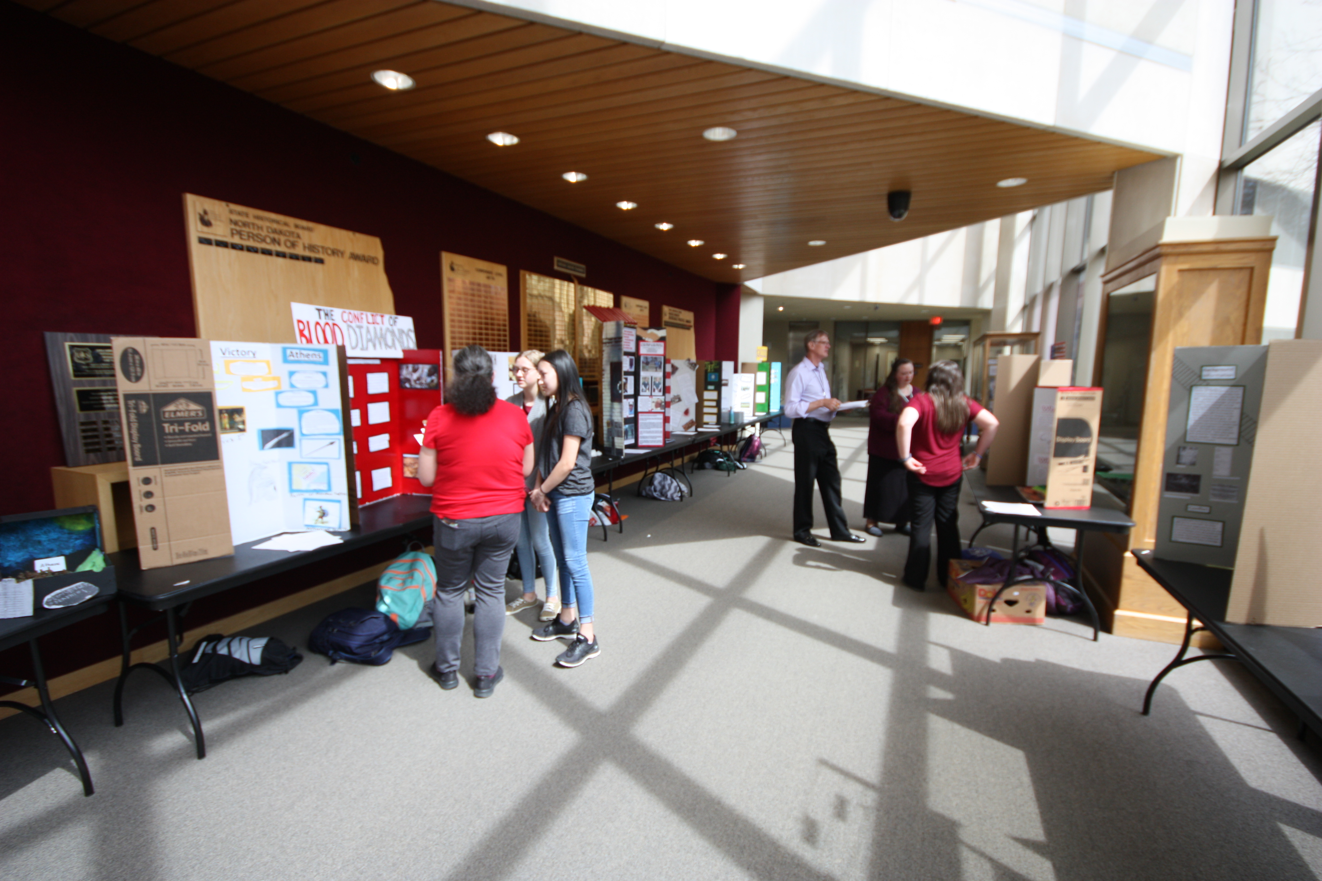ND Heritage Center with History Day contestant exhibits and judges. Judges inquire about the student's project and score according to the contest guidelines.