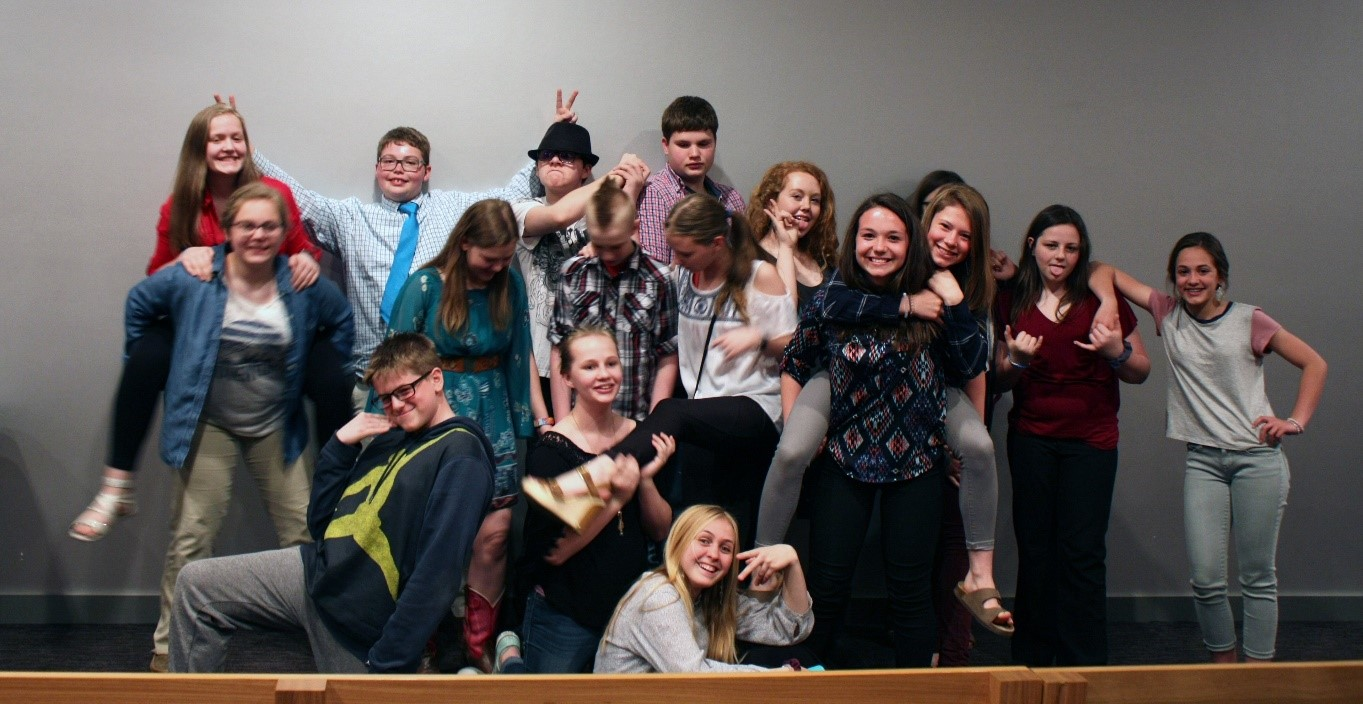 image is of National History Day students from 2018. The students are posing in a fun and silly postures.